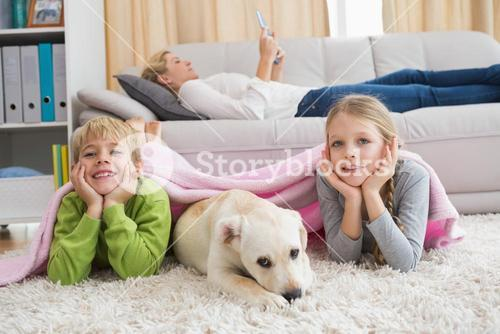 Cute silblings with their puppy on rug