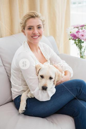 Happy blonde cuddling with puppy on sofa