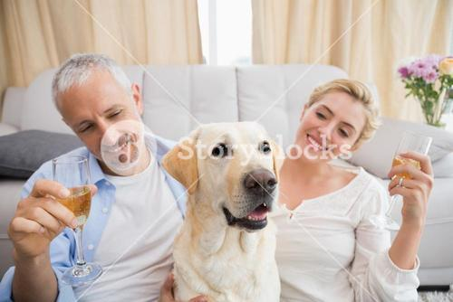 Happy couple with their pet dog drinking champagne