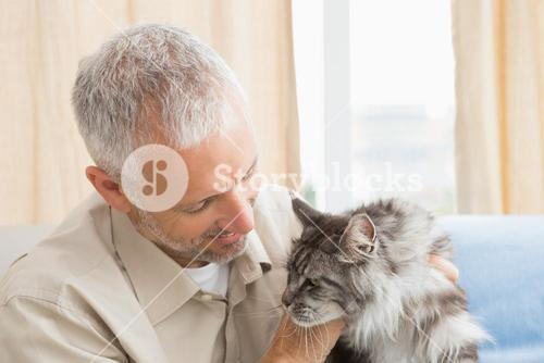 Happy man with his pet cat on sofa