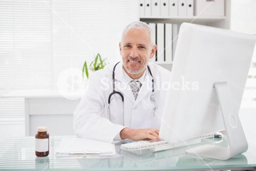 Happy doctor typing on keyboard
