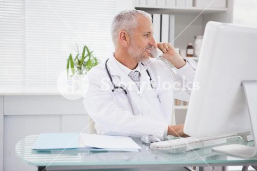 Smiling doctor phoning and using computer