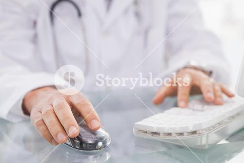 Doctor typing on keyboard and using mouse