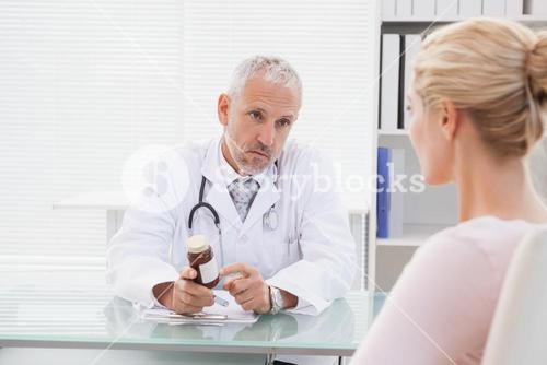 Concentrated doctor giving a prescription