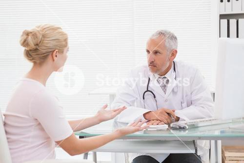 Patient consulting a serious doctor