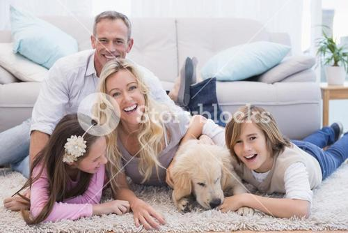 Laughting family with their pet yellow labrador on the rug