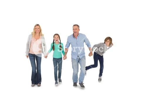 Happy family of four walking hand in hand