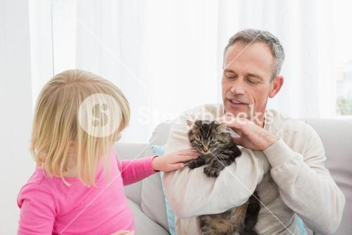 Happy daughter and father sitting with pet kitten together
