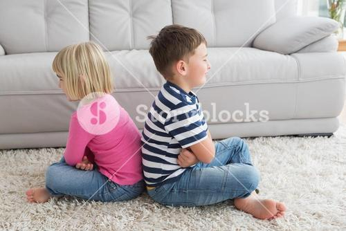 Irritated siblings ignoring each other
