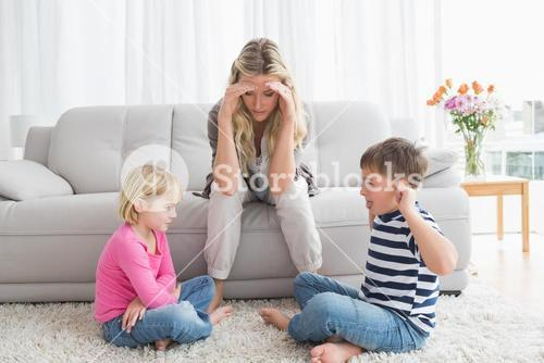 Fed up mother listening to her young children fight