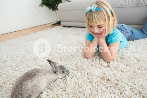Little girl lying on rug with rabbit