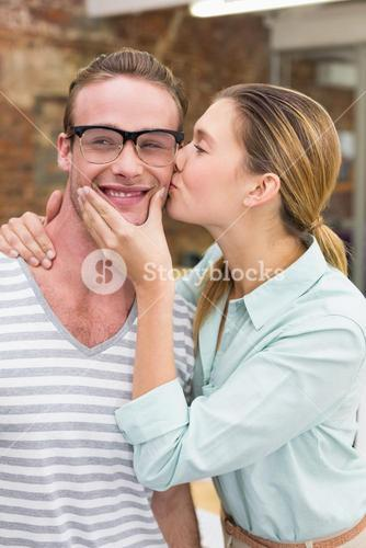 Woman kissing happy man in office