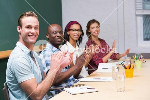 Colleagues clapping hands in meeting