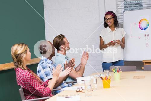 Casual business people clapping hands in meeting