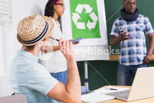 Creative meeting with recycling symbol on whiteboard