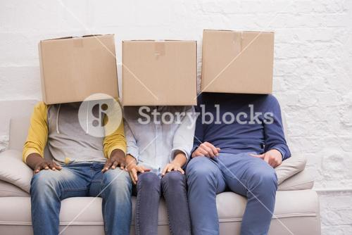 Casual people sitting on couch with boxes over heads