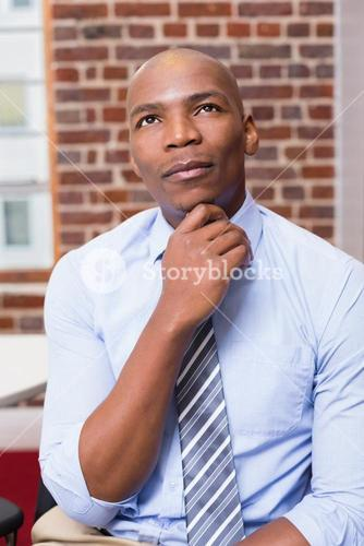 Thoughtful businessman looking up in office