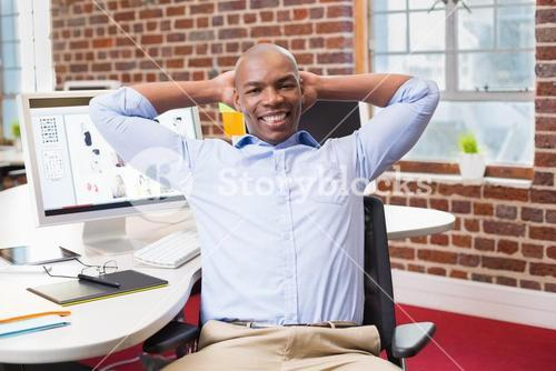 Businessman sitting with hands behind head in office