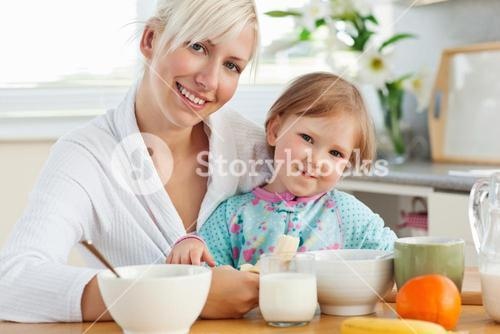 Radiant mother and daughter having breakfast
