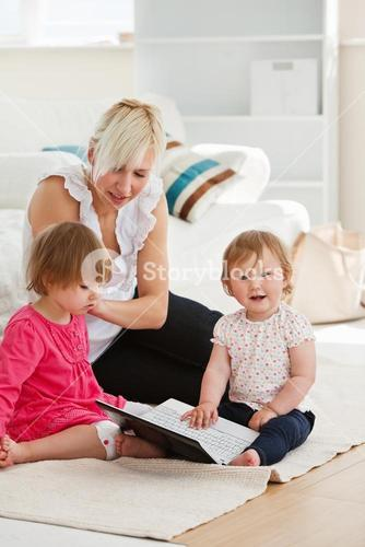 Goodlooking woman working with her children at laptop