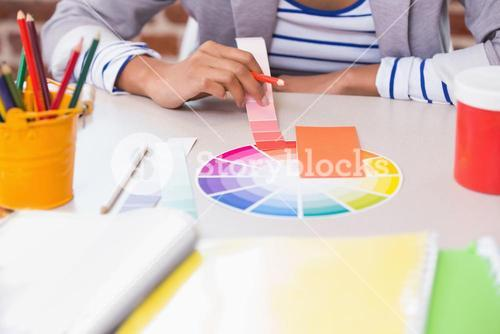 Mid section of designer with color samples at desk