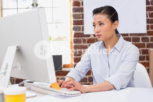 Concentrated woman using computer at desk