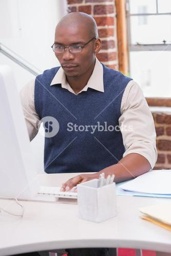 Serious businessman looking at computer monitor