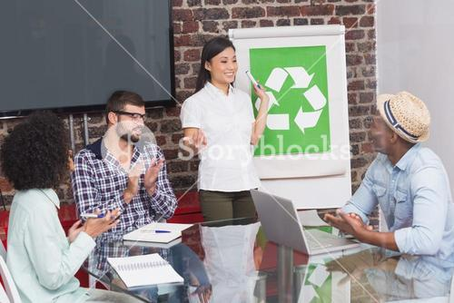 Team in meeting with recycling symbol on whiteboard
