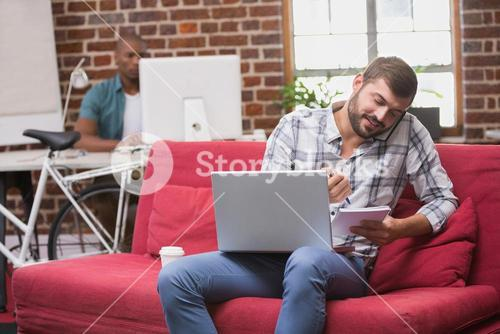 Man using laptop and mobile phone on couch in office