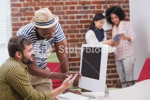 Casual people using computer in office