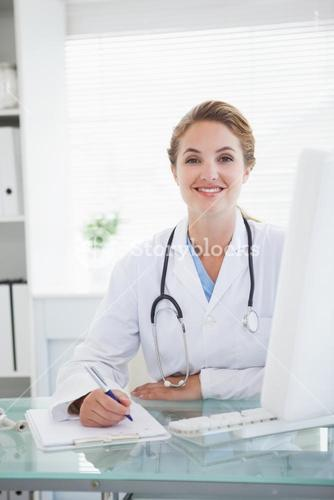 Doctor smiling as she takes notes