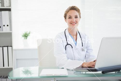 Doctor smiling as she types