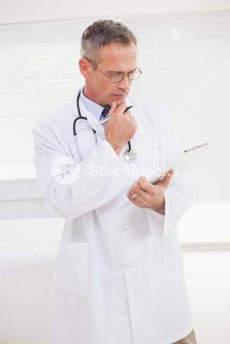 Focused doctor looking over medical notes
