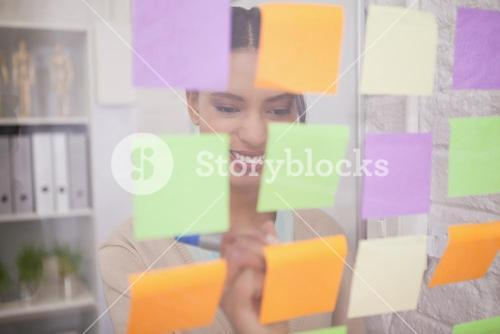 Smiling businesswoman writing on sticky notes on window
