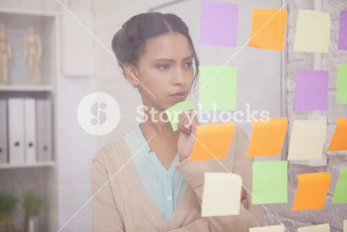 Thoughtful businesswoman looking at sticky notes on window