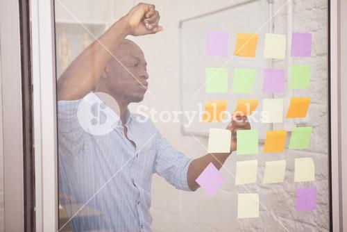 Thoughtful businessman looking at sticky notes on window