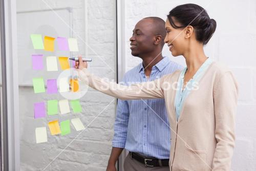 Creative businesswoman writing on sticky notes on window