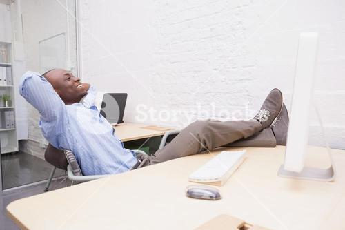 Businessman relaxing at desk and smiling