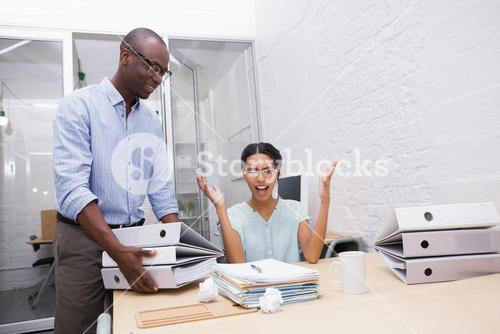 Businesswoman surprised with stack of folders at desk