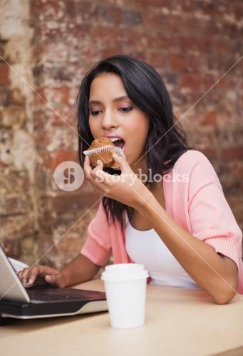 Woman eating a muffin and having a coffee