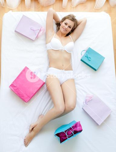 Erotic woman lying in bed with shopping bags