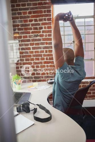 Casual businessman stretching in chair