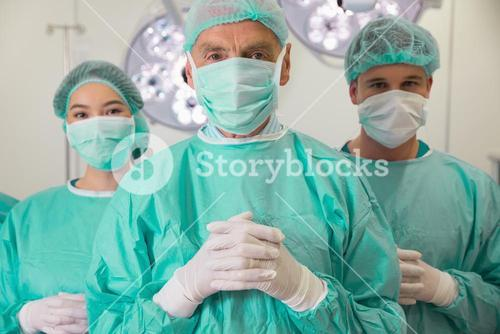 Medical student and lecturer looking at camera in scrubs
