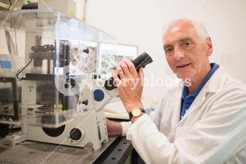 Biochemist using large microscope and computer