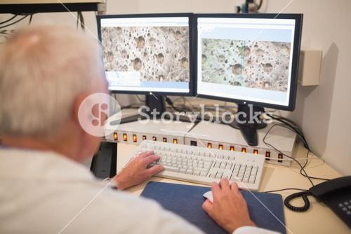 Biochemist looking at microscopic images on computer