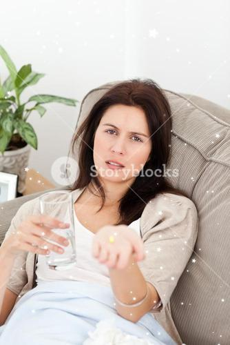 Sick woman showing a pill to the camera