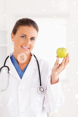 Gorgeous brunette doctor looking at a green apple