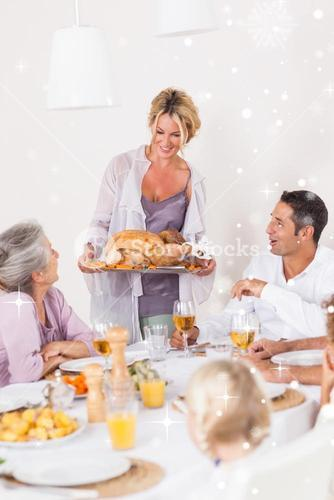 Composite image of mother bringing turkey to dinner table