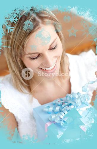 Delighted young woman holding a present sitting on the floor