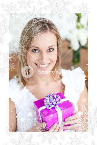 Charming young woman holding a present sitting on the floor